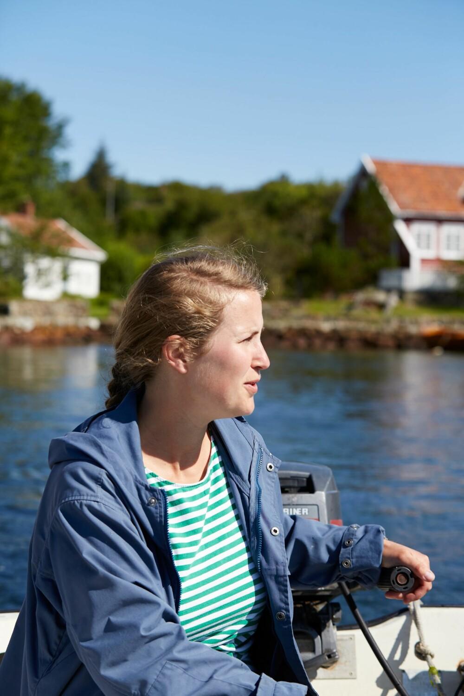 I BÅTEN: Eieren er i sitt ess når hun styrer båten over sundet mellom Loshamn og Sandøy.  Båtlivet bringer frem gode barndomsminner.