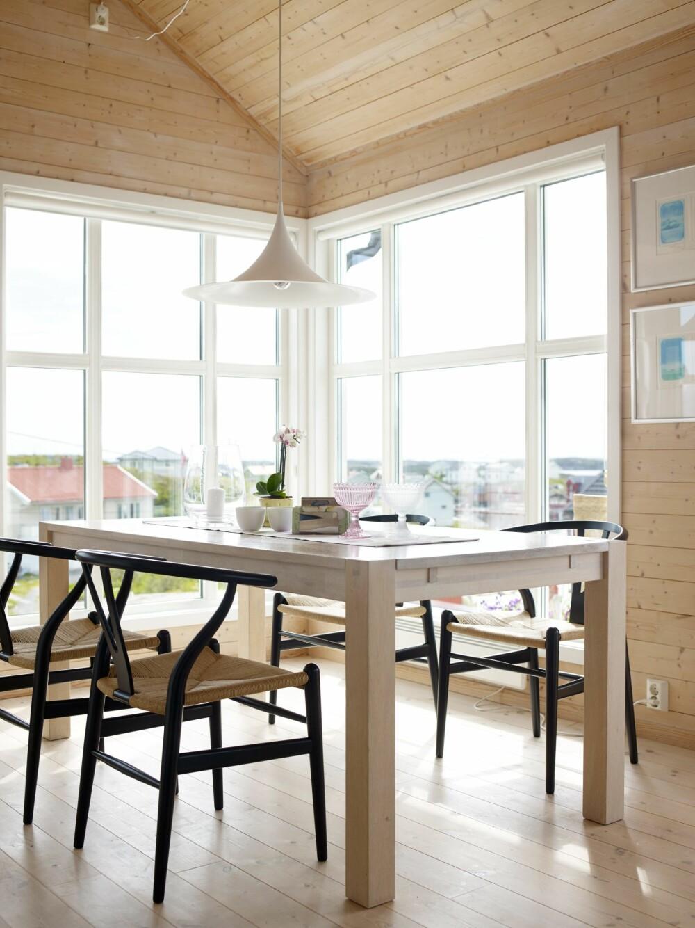 HØY HIMLING: Det er virkelig høyt under taket. Anne Karin samler ofte venner rundt bordet til krabbelag. Y-Stolene er designet av Wegner, kjøpt hos Berge Interiør. Pendel fra Rom til Rom. Spisebord fra Bohus.