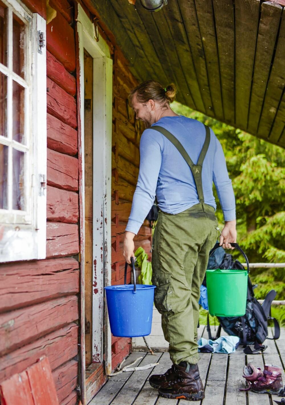 HENTER VANN: Gunnar må gå til brønnen som ligger noen meter bak hytta for å hente vann. (FOTO: Sveinung Bråthen)