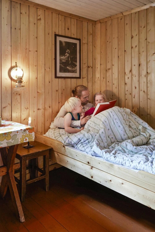 FAST INNSLAG: Det er like stor stas hver eneste kveld når Gunnar legger seg for å lese høyt fra eventyrboken for barna Boas og Naomi. Sengen er plassert rett ved kjøkkenbenken, som skiller de to sovesonene i hytta. (FOTO: Sveinung Bråthen)