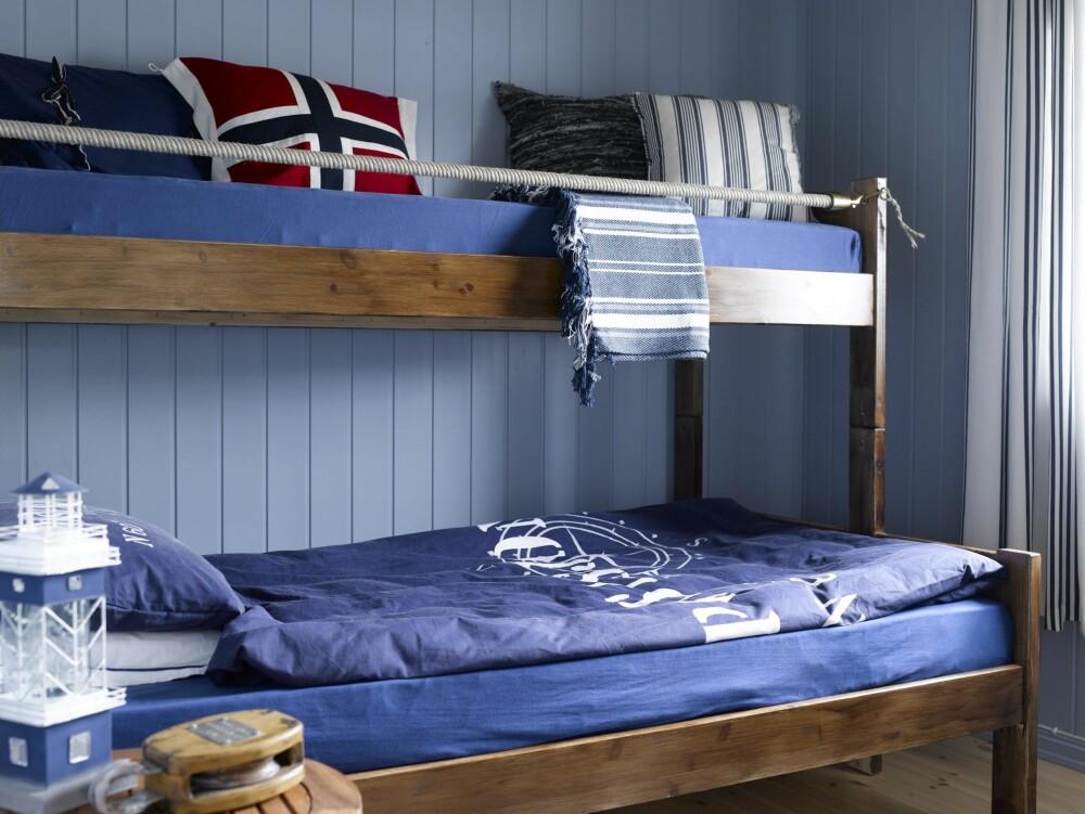 MARITIMT: På dette soverommet pusset de opp et klassisk gutterom til et lunt og mer voksent preg. Den mørke beisen på sengen harmonerer fint med de blå veggene. Legg merke til tauet øverst. Et grep for å understreke det maritime preget.(FOTO: Per Erik Jæger)