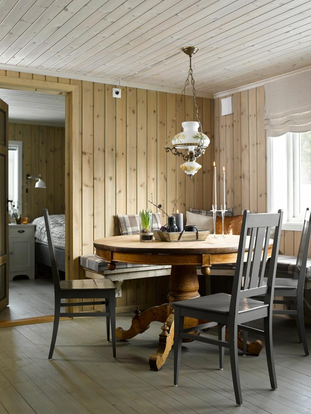 SAMLINGSPUNKT: Spisebordet har vært på hytta lenge. Lampen etter Grethes svigerfar fikk strøm for lenge siden. Spisebordet er behandlet med naturell Osmo hardvoksolje. Stolenes grå nyanser tar opp fargen fra de tynne listene i dørene.
