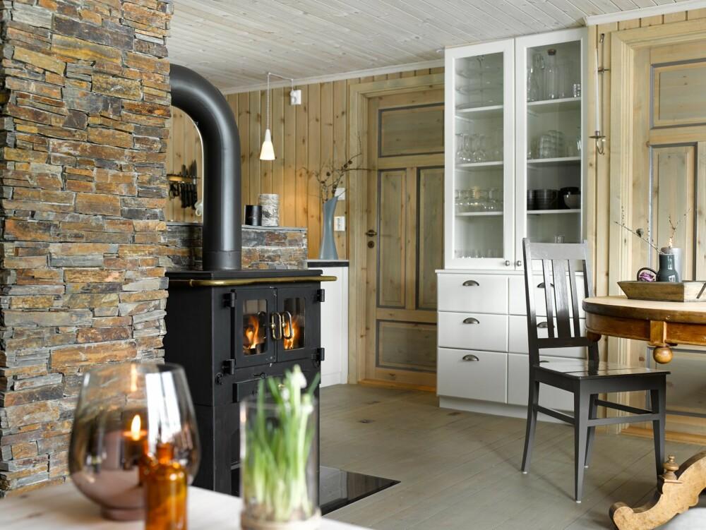 ÅPNET OPP: Kjøkkenet er en del av det sosiale flerbruksrommet. For å skjule middagsrotet på kjøkkenbenken, er benken trukket opp i høyden. Pipen er kledd med BACstone, Quatro Rondane, som er skifer med mye rustpreg, fra Norfloor.