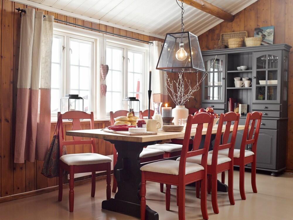 SPISESTUEN: Alle møblene i spisestuen sto på hytta fra før. Lena og Edvard hadde malt spisestuestolene røde, og de ønsket at det skulle gå en rød tråd gjennom interiøret. Vitrineskapet og understellet på spisebordet ble malt grått med Nordsjö Professional dør, list, panel 15. Merle, glans 15. På gardinene lappet de på et linstoff slik at gardinene er todelt i fargen. Lampen over spisebordet er fra Lama.