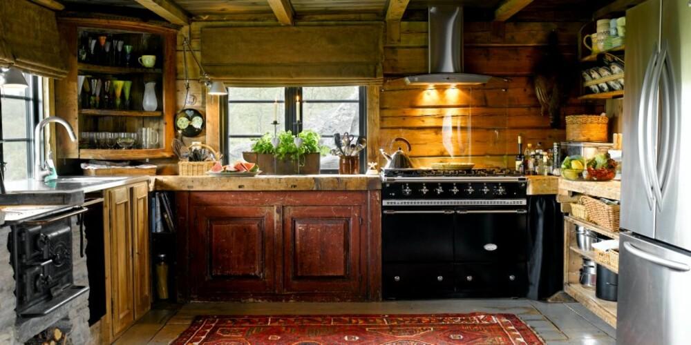 MATERIALMIKS: Spennende og harmonisk materialmiks med gammel svartovn i jern side om side med en moderne oppvaskmaskin. Mot skifer og røffe og rustikke møbler i tre, danner material-og og møbelmiksen et frodig og vellykket personlig uttrykk.