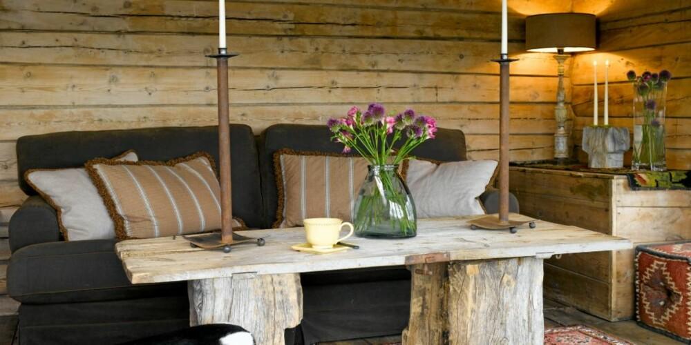 SELVGJORT: Bordet i stua er laget av en gammel dør som har tilhørt huset. De kraftige stokkene som er brukt til bordbein er funnet på Hardangervidda. Lysestakene er designet av mannen i huset, Helge, og er fra Symbiose Design.