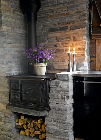 TRADISJONSRIK VARMEKILDE: En gammel vedfyrt svartovn gir mulighet til å både koke og bake på gamlemåten. Muren rundt ovnen er bygget opp av bruddskifer.