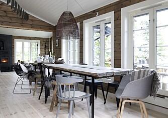BLIKKFANG:  Store vindusflater på kjøkkenet og i stuen gir godt med lysinnslipp og god romfølelse. Her kan den fine utsikten nytes fra alle sitteplassene. Bordet er selvkomponert av understell fra Ikea og kraftige, værslitte plank fra Fru Blom Design. Randi har kombinert forskjellige stoler for å unngå et nokså standard uttrykk. Lampen er en vareprøve fra en interiørgrossist. Peisen fra Hwam, har bakerovn over brennkammeret.