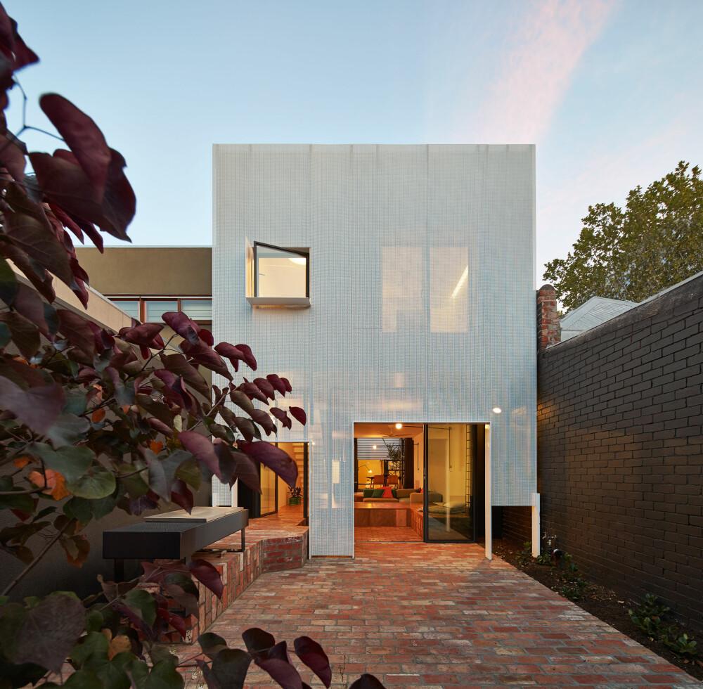 DRAPERT: Fasaden som vender mot solen er kledd i et metalldraperi, som både skjermer interiøret mot solen men samtidig slipper lyset mykt inn.