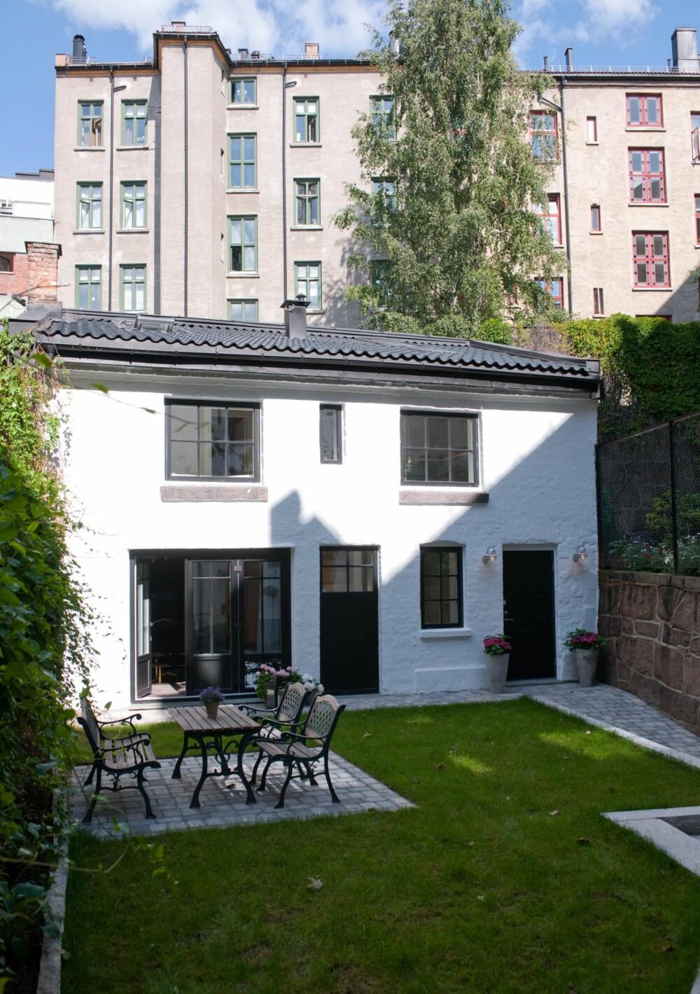 ENESTÅENDE ENEBOLIG: Den ombygde stallbygningen ligger omkranset av høye bygårder midt i Oslo. I forbindelse med renoveringen ble både vinduskarmene og dørene malt svarte.