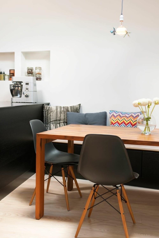 OPPSIRKULERT SPISEBORD: Bordet er tegnet av interiørdesigner Elisabeth Bjørge, og er laget av teak fra et opphugget cruiseskip. Den plassbygde sittebenken langs kortveggen fungerer også som oppbevaringsplass for tallerkener og annet løsøre.