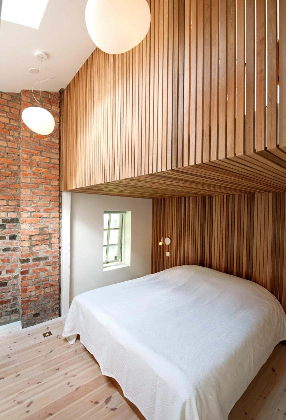 INTIM SONE I LUFTIG ROM: Spilene av sedertre opptrer både som sengegavl, veggkledning og gelender. Herfra er det åpen forbindelse til hjemmekontoret i etasjen over. Belysningsplan og lamper er ved SM Lys v/ Kenneth Fossum i samarbeid med arkitektene.