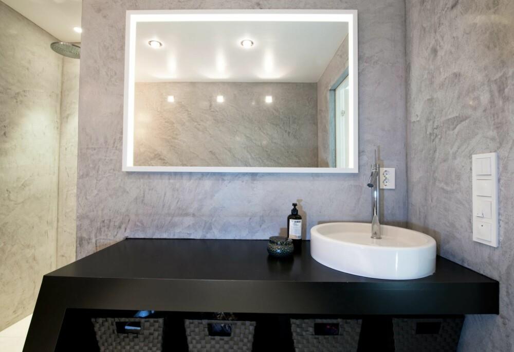 BAD MED MARMOREFFEKT: Baderomsveggene består av marmorisert betongpuss. Det uregelmessige mønsteret skaper variasjon og spenning i et ellers minimalistisk innredet rom. Det er lagt baderomsplater under betongpussen for at våtromsnormen skulle overholdes.