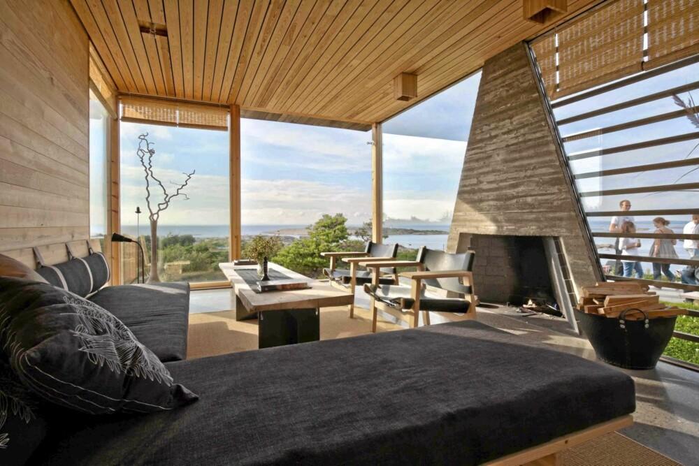 VIDSYNT: Stuen åpner seg med store vinduer og skyvedører mot utsikten og atriet. Legg merke til den skulpturelle, prismeformete peisen.
