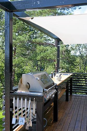 TRIVSEL I DET FRI: Den solide benken er sentrum i det praktiske utekjøkkenet. Det skjermes av et figurskåret solseil.