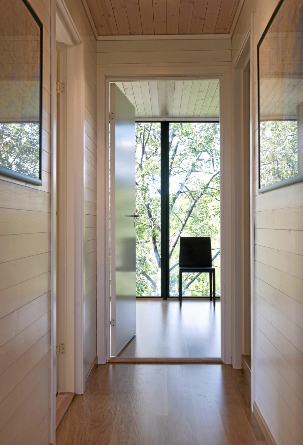 SIKT TVERS GJENNOM: Fra kjøkkenet ser du rett gjennom hytta og til vinduene i den høye fasaden som vender rett mot furuskogen.