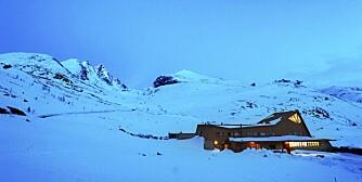 """KLATRERNES ELDORADO GJENOPPSTÅR: Et nytt """"fjell"""" i Jotunheimen. Da Turtagrø Hotel 23 januar 2001 var inn i sin 113 sesong(!) brant hovedbygningen ned til grunnen. Nå er er det gjenoppstått i arkitektfirmaet Jarmund& Vigsnæs spreke strek. Hurrungane med blant annet Skagastølsryggen med Storen i bakgrunnen. Til høyre Dyrhaugsryggen. Dette området har vært en kjær base for fjellfrelste fra mange land i over hundre år."""