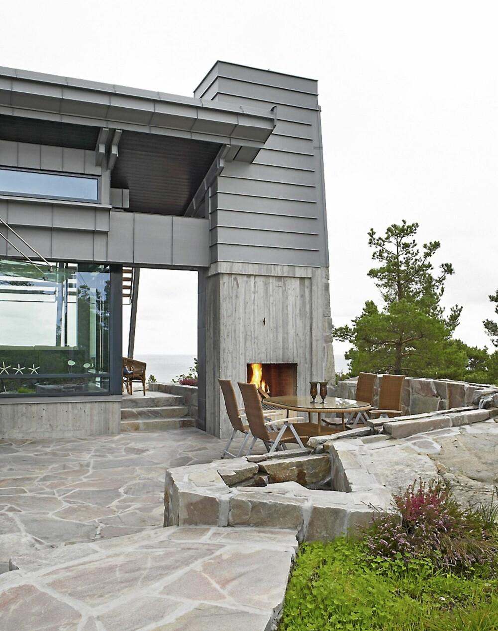 UTEROM: Peisen er en del av takets bærekonstruksjon. Den utvendige formen på bygningen skaper rom ute. Om det blåser påfremsiden, trekker familiengjerne hit. Skiferen er hentet fra et stedlandsdelen, nærmere bestemt Froland