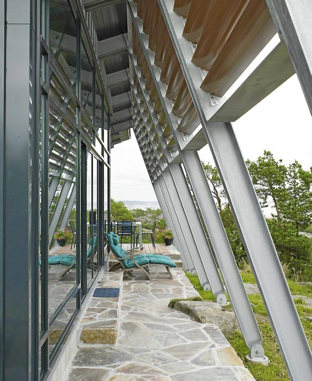 BLENDING: Solavskjermingen er montert mellom bærebjelkene, og holdt i tre for å dempe speilingen av glassfasaden. Betongplattingen er formet etter fjellet.