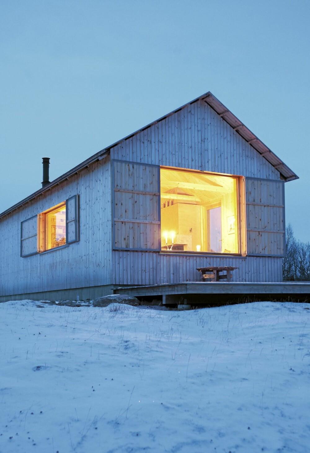 MAGISK ØYE: I skumringen, i den blå timen gløder det i det store stuevinduet rett mot sør. Hytta er helt moderne, men med røtter dypt forankret i norsk byggeskikk.