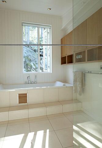 PRIVAT SONE: Badet er hvitt og lyst, men eikeskapene tilfører interiøret varme.