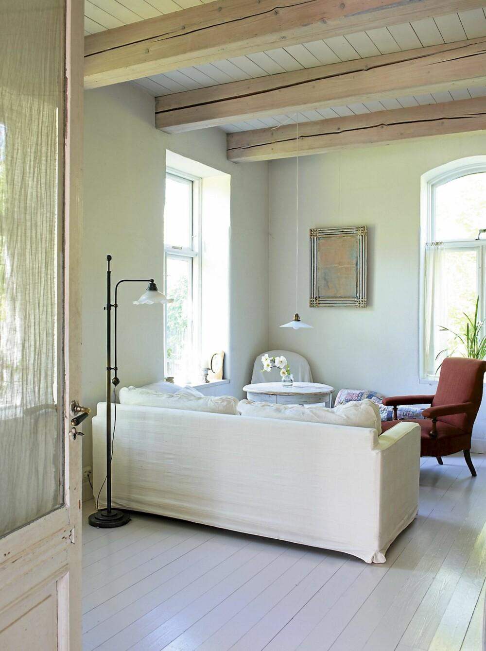 KOMPONERT: Stuen er sval og har rommelig gulvplass. Gulvet er malt med høyglansmaling. Møbler og lamper er funnet på loppemarkeder. Bildet på veggen er malt av Hilde Grønner Flikke.