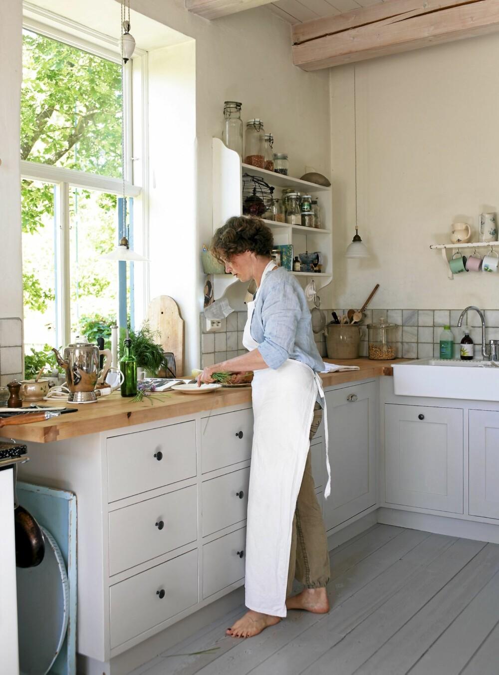 HOVEDROMMET: Kjøkkenet er husets hjerte. På den solide arbeidsbenken lager Camilla Jensen retter til familien og for kokebøker, for tiden hoder hun på med en frokostbok. Kjøkkeninnredningen har mannen snekret, før den kom på plass brukte de gamle vinkasser. Vasken er fra Ikea.
