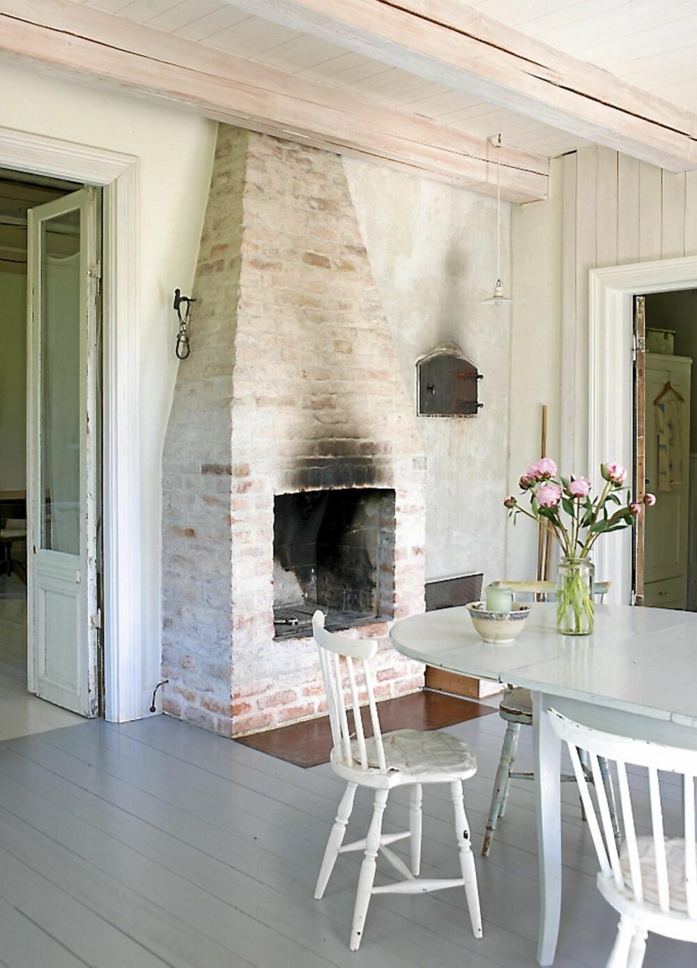 VARMESTED: Den store murstein peisen er mørtlet. Bordet er funnet på loppemarked, det samme er stolene rundt og alle er forskjellige. Døren til høyre fører inn til stuen.