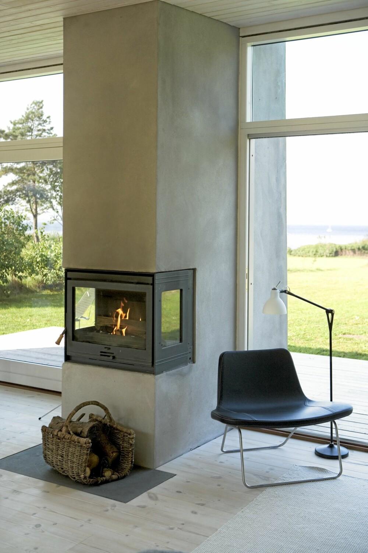 LEKKER PEIS: Peisen fra Dovre er Karinas favorittmøbel. - Jeg synes det er fantastisk å kunne sitte i sofaen og se ild og vann samtidig. Peisen skiller stuen fra kjøkkendelen. Lenestolen er fra Hay, og leselampen Fortebraccio er fra Luceplan.