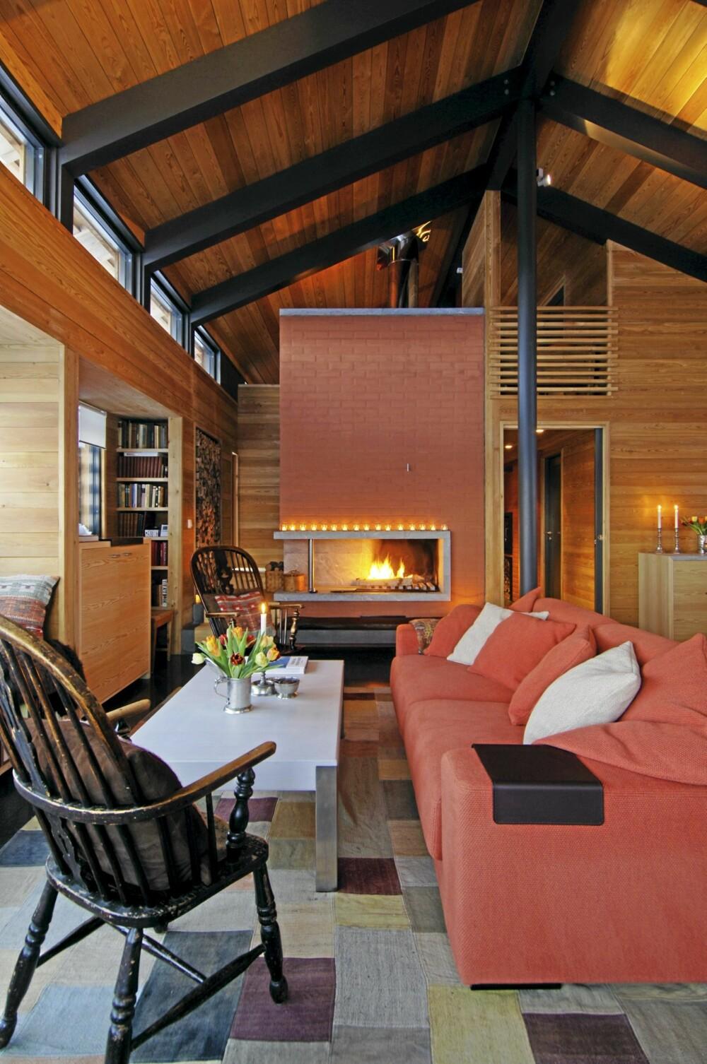 FRODIG MIKS: Den terrakottafargete peisen er sentrum i stuen. Taket bæres av gråmalte stålsøyler og limtredragere. Flere soverom på hemsen. Sofa fra Exo Møbelstudio.