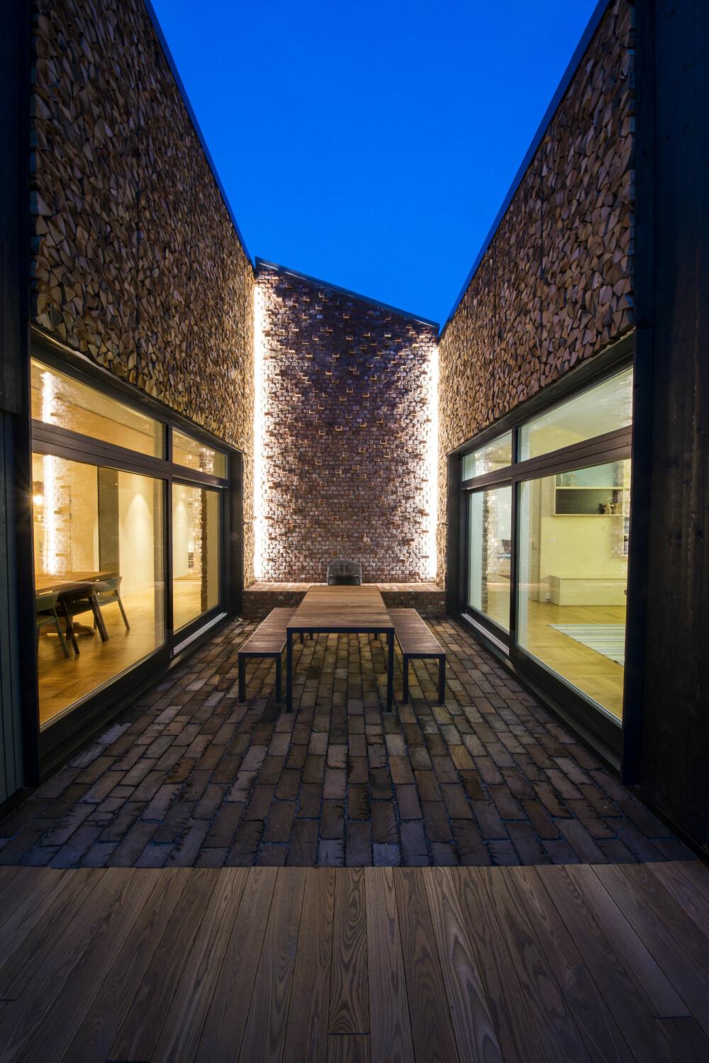 STEMNING: Selv om det er et moderne, og på mange måter strømlinjeformet hus, er det lagt vekt på stemningsskapende effekter. Murstenene i endeveggen i atriet kommer fra et gammelt fjøs. I de andre veggene er det lagt vedskier, som også kan brukes til å fyre med i utepeisen innerst i rommet.