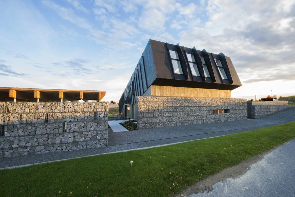 SKRÅSTILT: Husets form er optimalisert for å utnytte solenergien best mulig. I muren mot veien er det brukt sprengstein fra et steinbrudd i nærheten.