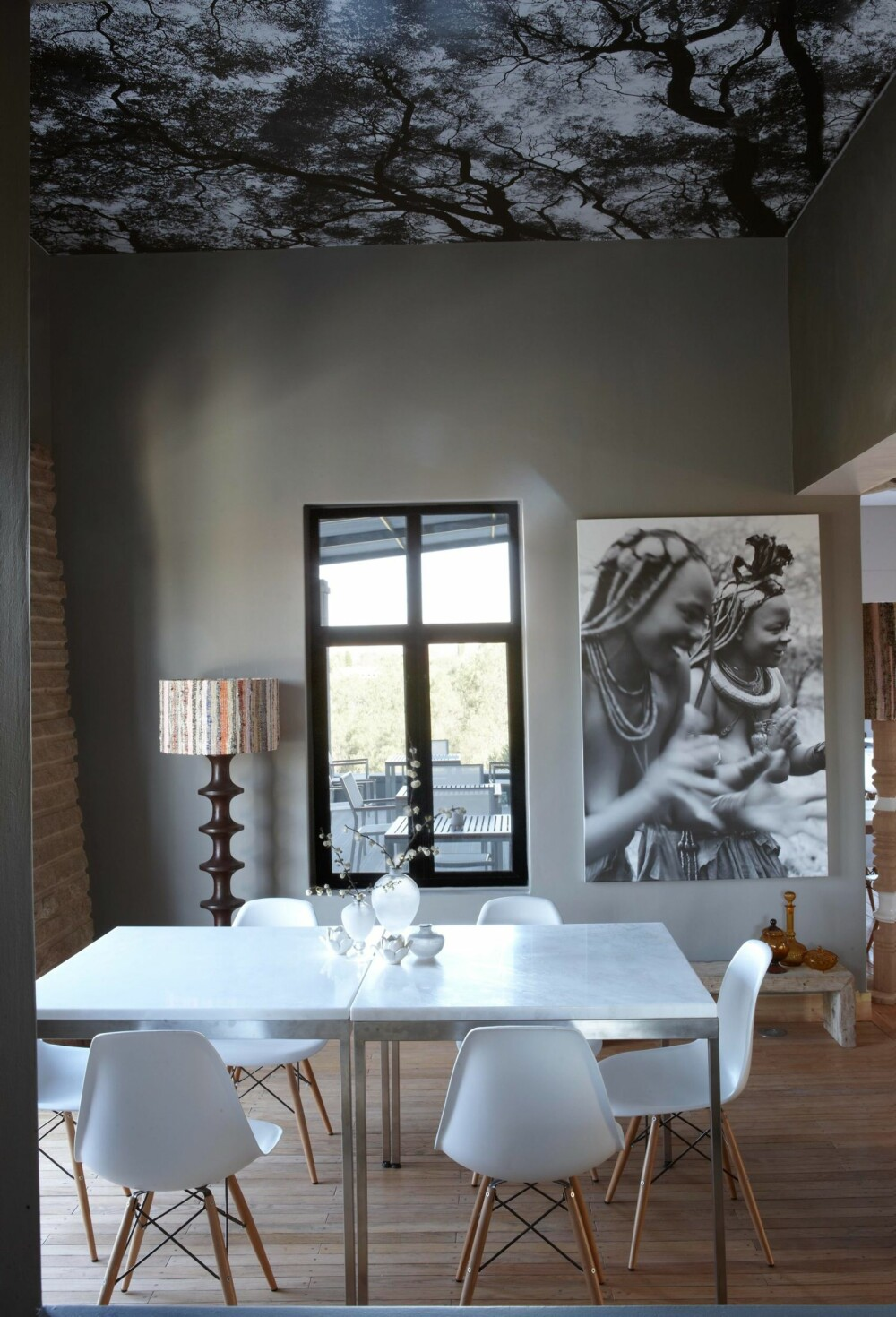 TAKTAPET: I restauranten er taket tapetsert med et svart-hvitt bilde av et tre. Fotograf er Micky Hoyle. På veggen henger et annet av bildene hans. Enkle bord med marmorplater er omgitt av gjenkjennelige DSWstoler med understell i tre, designet av ekteparet Eames.