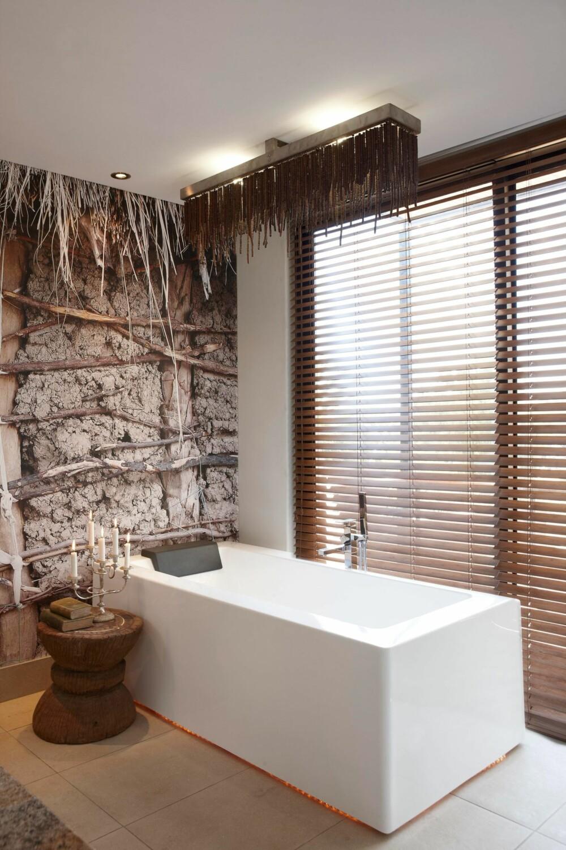MOT VEGGEN: Det moderne badekaret med ledbelysning nær gulvet får stå relativt alene mot veggen som illustrerer tradisjonell byggkonstruksjon. Lampen har «greiner» som tar opp detaljer fra veggen.