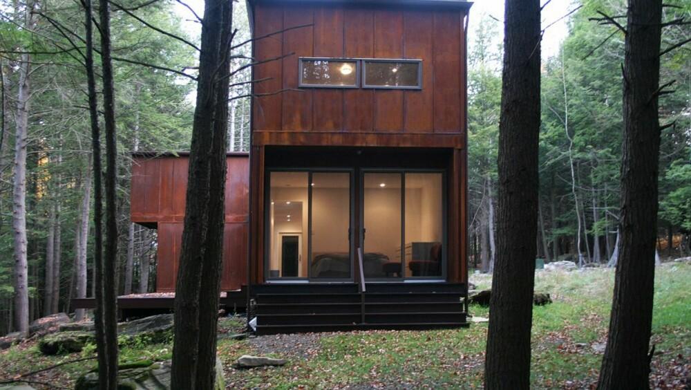 TO ENHETER: Huset består av to enheter som er koblet sammen av en glassbro med integrert uteplass. store glassvinduer åpner opp mot skogen rundt.