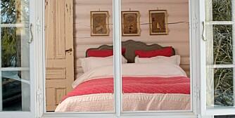 HOVEDSOVEROM: I hjørnerommet ligger hytteeiernes soverom, med mørk gråmalt sengegavl, bringebærrødt sengeteppe og brodert, indisk sengetøy. På veggen henger gamle indiske dokumenter med fargerike stempler.
