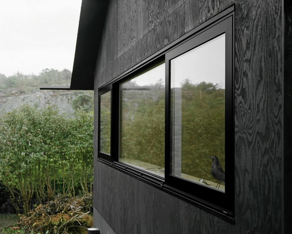 ET HUS MED RENE LINJER: Vinduene går som lange, sammenhengende bånd i fasaden. Legg merke til den spesielle utstikkende takrennen i aluminium.