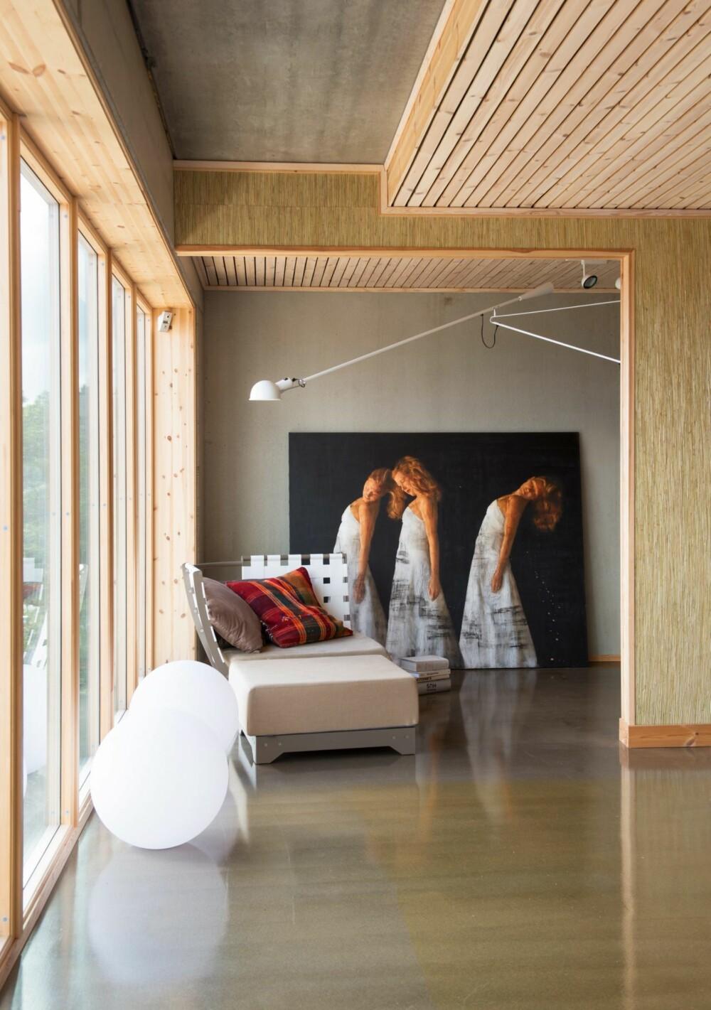 FRITT FOR HVITT: Store vinduer og rikt lysinnfall gjør at interiøret føles lyst, selv uten hvite flater. Maleriet er ved Per Fronth. Den vegghengte lampen er fra Flos, den modulbaserte sjeselongen Vino fra Sundays Design.