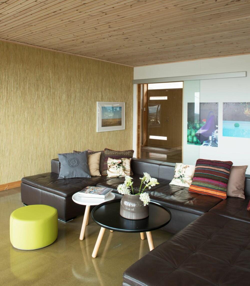 BETONG, GRAN OG STRÅTAPET: Stuesonen i allrommet vender mot utsikten. Sofaen er fra BoConcept, sofabordene fra Normann Copenhagen, puffen fra Sundays Design.