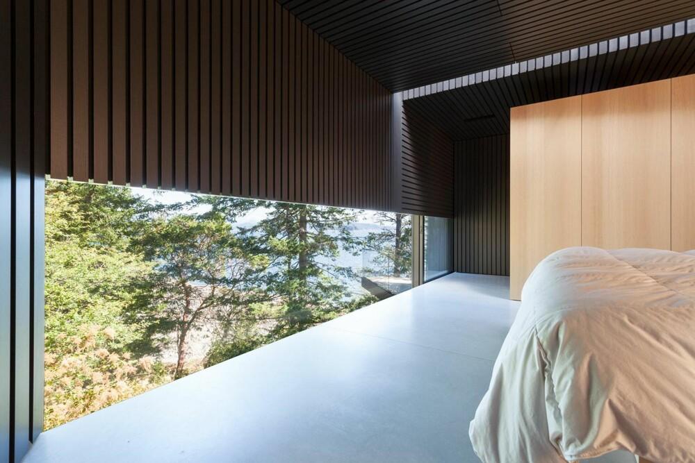 SOVEROMMET: På soverommet slipper lyset inn både gjennom det lavtsittende vinduet og slissen i taket. (FOTO: James Dow/Patkau architects)