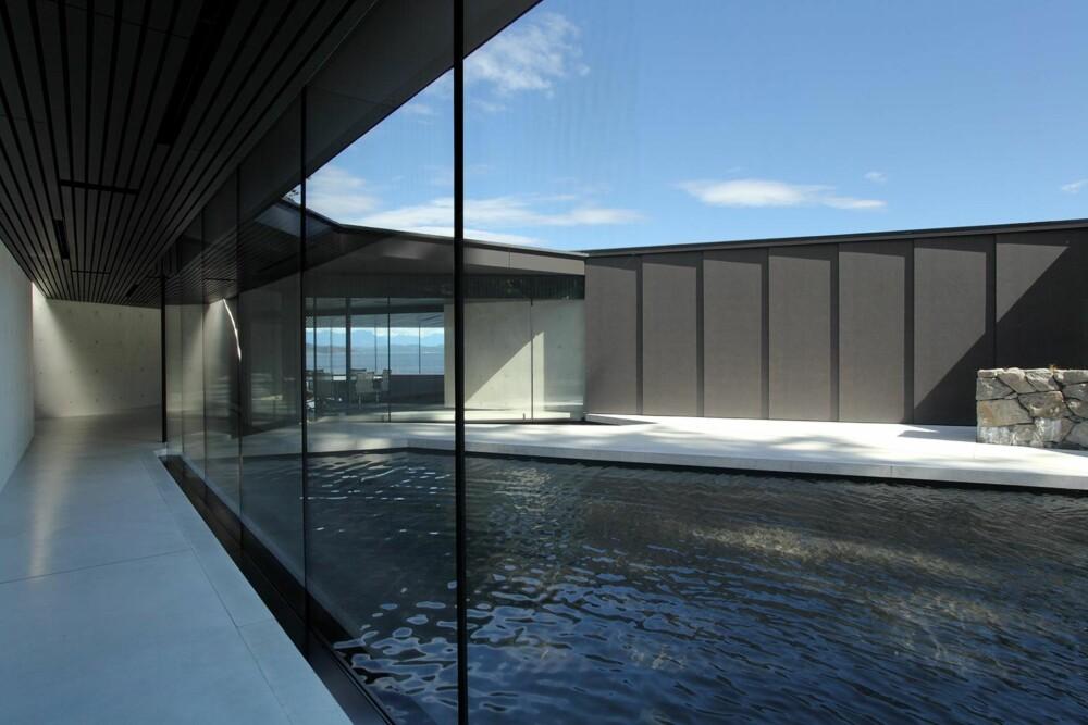 GRUNNVANNBASSENG: Grunnvannet har fått lov til å renne fritt gjennom tomten, og blir blant annet samlet opp i dette vannspeilet som ligger midt inne i bygningen. (FOTO: James Dow/Patkau architects)