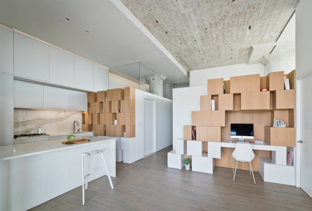 ASYMETRI: Bruken av de asymetriske boksene gir et levende interiør som samtidig er holdt stramt ved bruk av hvite flater. Stramheten forsterkes av at skapdørene på kjøkkenet ikke har håndtak.