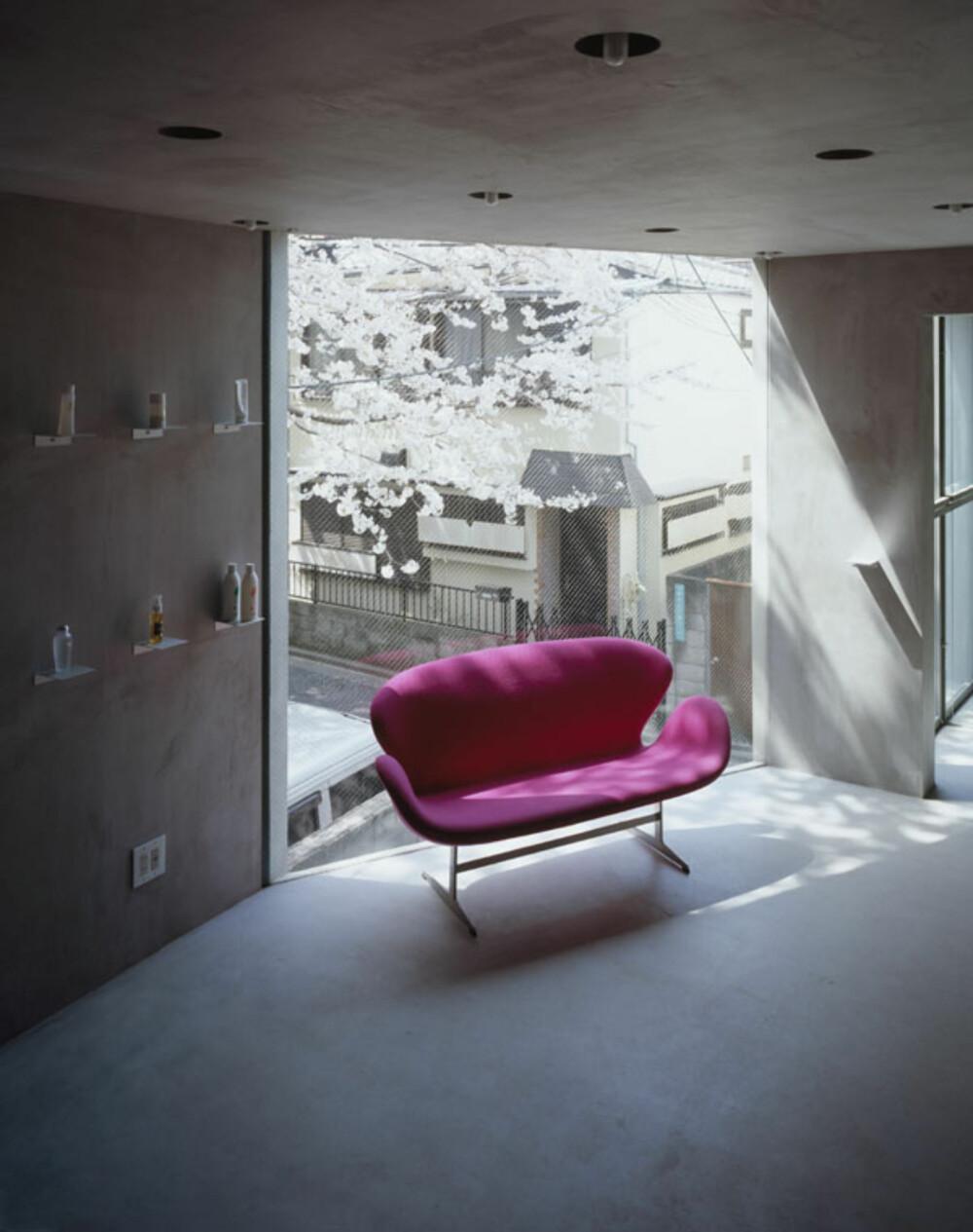 FARGEKLATT: En knall rosa sofa fungerer som en fargeklatt i det ellers nakne interiøret.