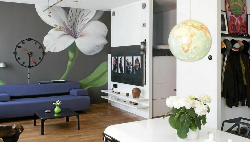FONDMALERI: Den veggmalte blomsten ved Jonas Wickman/ Arcanum Swedish Design fanger blikket. Hjemmekontoret er ute av syne. Sofaen er fra Cor. Vegglampen er fra Jieldé, mens takskinnen er fra Aero Design.