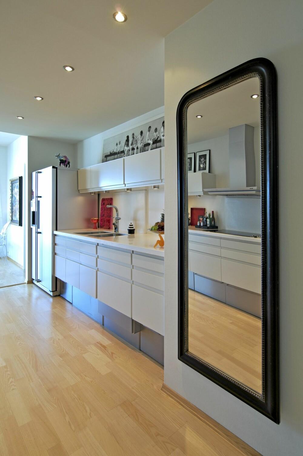 GJENNOMGANG: HTH Straight-kjøkkenet ligger midt i boligen og det har benkeplate og bakplater i hvit corian. Hvitevarer i aluminium.