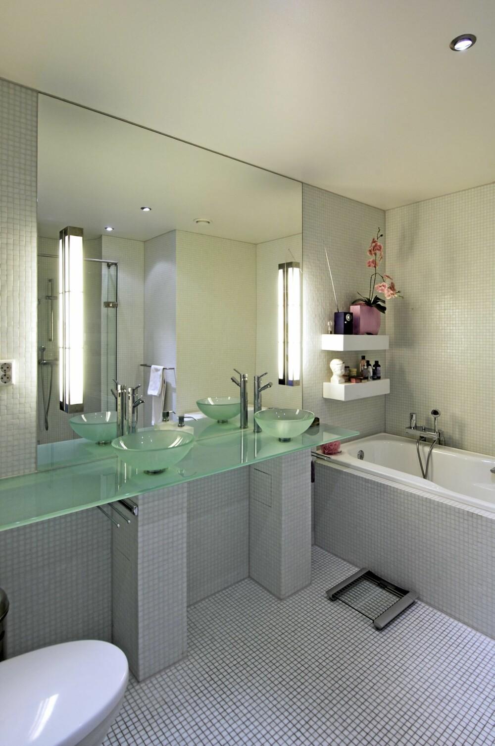 GLASSKLART: Hvit glassmosaikk er brukt på vegger og gulv i begge bad. Glass i servanter og benkeplater - og i dører.