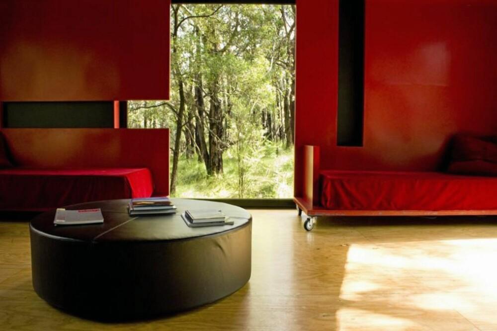 FARGEKLATT: På oppholdsrommet har arkitekten valgt å bruke rødt på de mobile skyvedørene med innebygde sofaer.