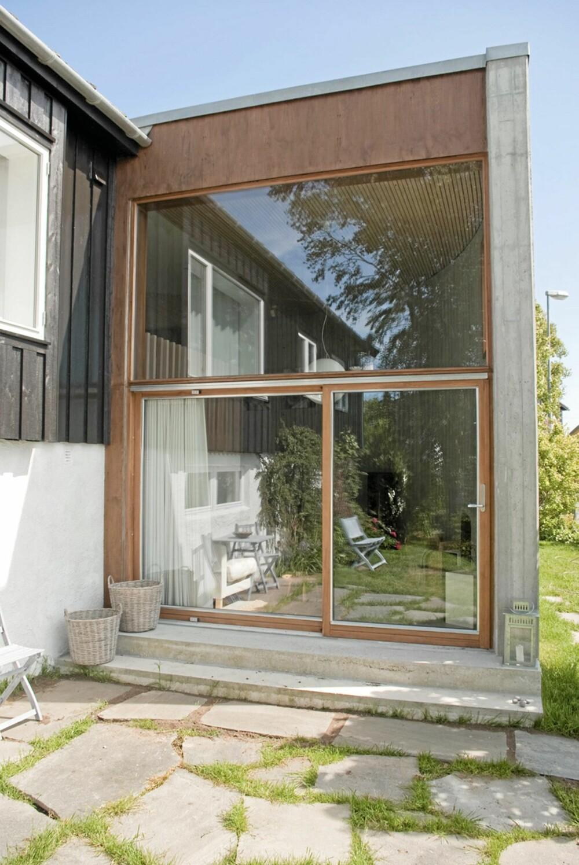 UT MOT HAGEN. Endeveggen ut mot hagen er i glass og slipper naturen inn. Her er det også dør ut til hagen.