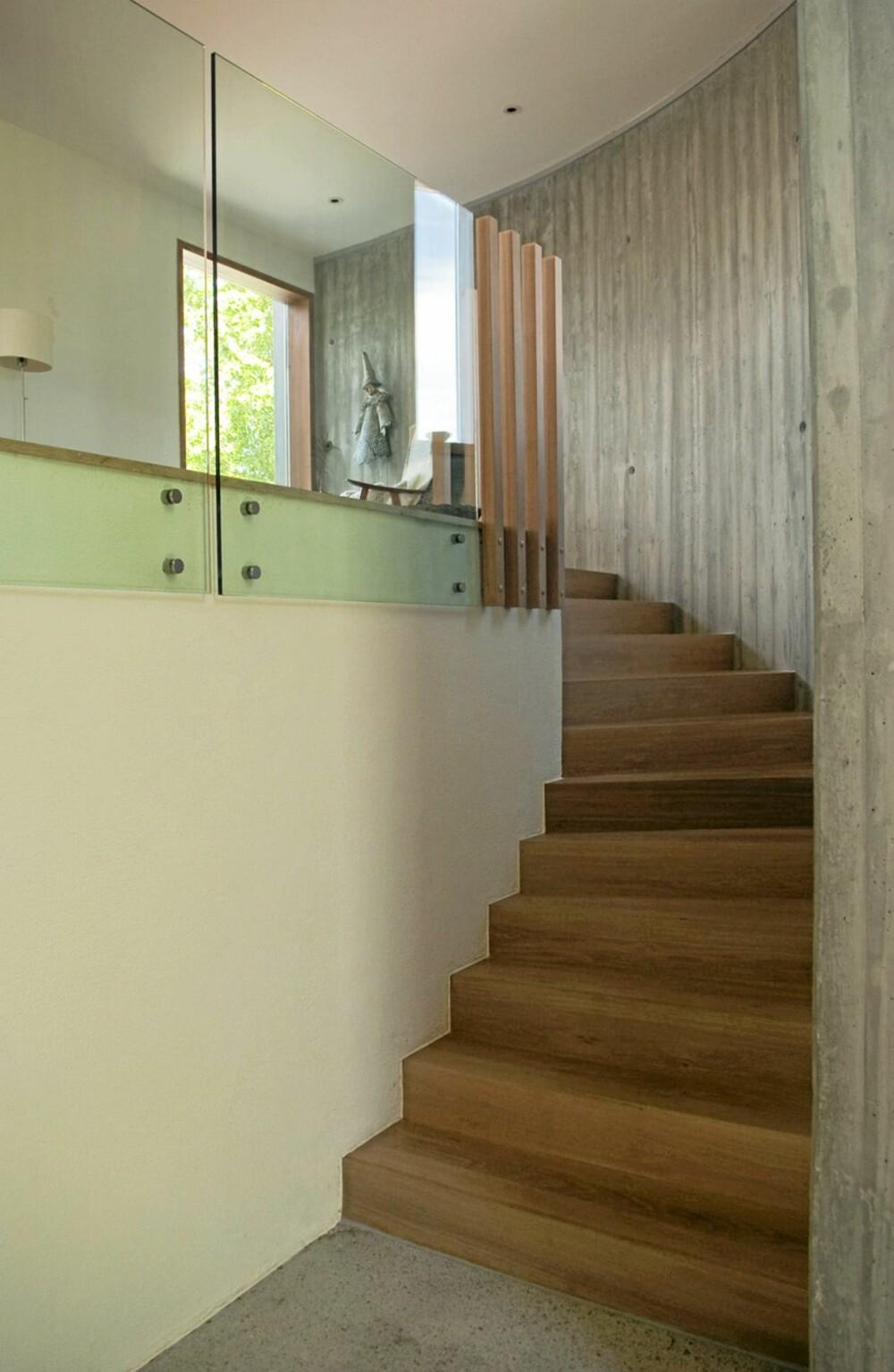 OPPTRAPPING. Trappen fører fra første til andre etasje. Rekkverket er av glass og trespiler.
