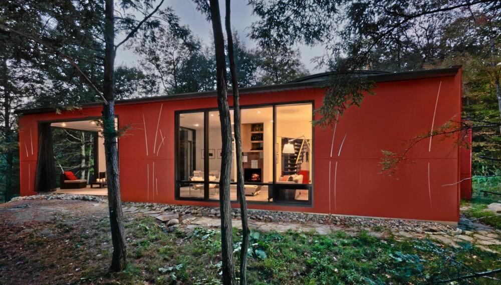 USJENERT: Den røde funkishytta ligger uforstyrret til med store vinduer som åpner opp mot skogen.